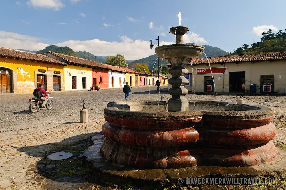 A Spanish colonial fountain on a cobblestone street in Antigua, Guatemala.
