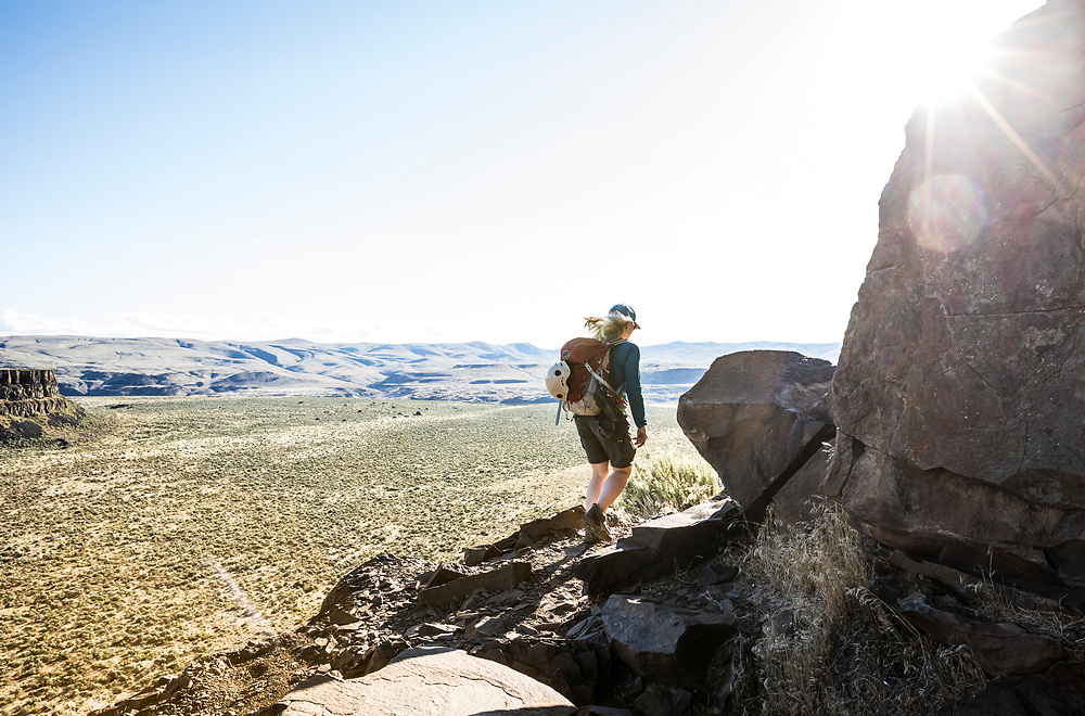 A woman hiking the climbers trail around Sunshine Wall in Echo Basin / Frenchmans Coulee, Eastern Washington, USA.