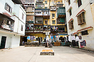 """Concrete yard in a local quarter of Hanoi, Vietnam, Asia. Buildings follow a classic hanoian's architecture called """" khu thap the""""(KTT). Every window have an terrace extensions with metal grids"""