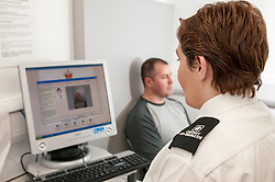 Suspect being photographed for identification in Middlesborough police station