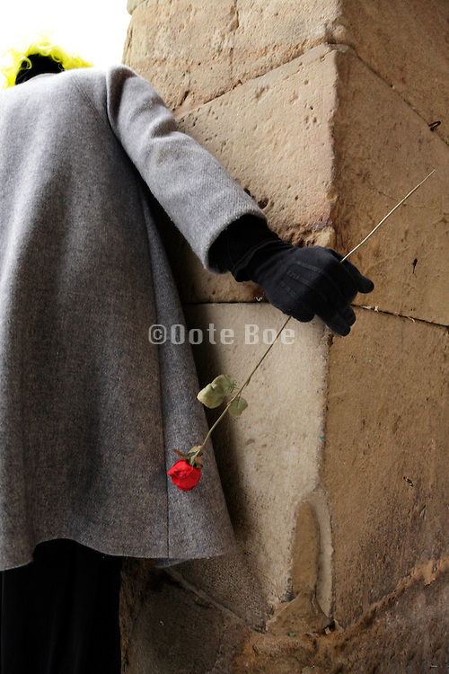 person with red rose that hides behind a pillar