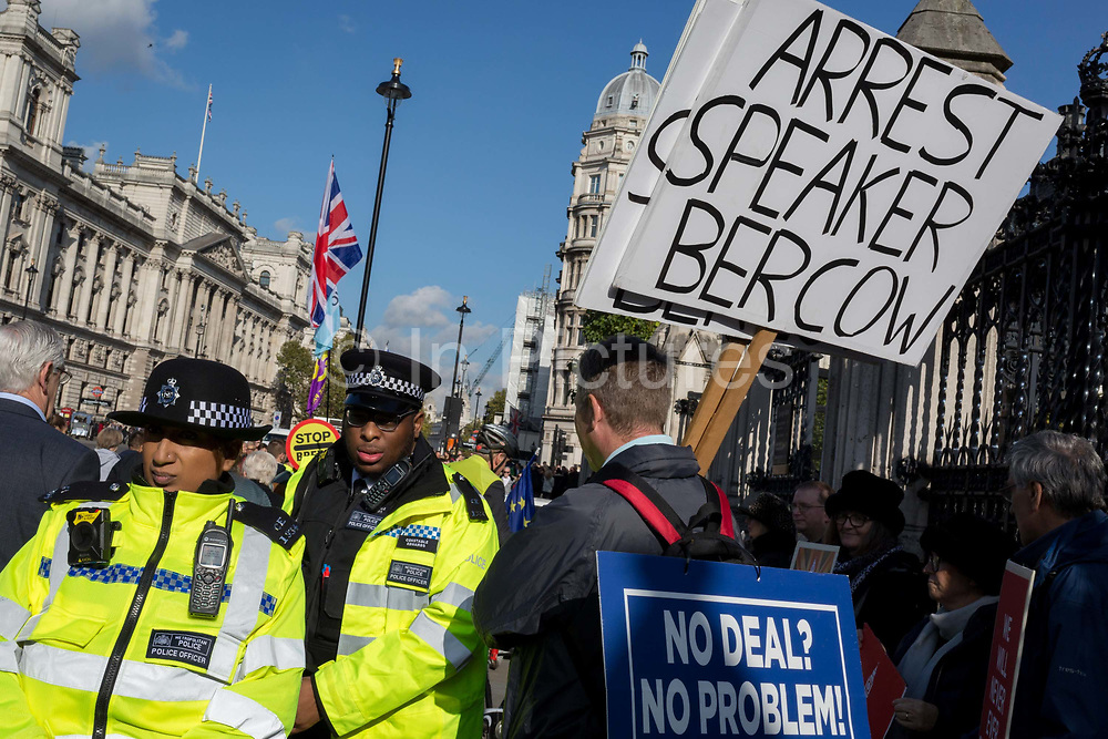 """Twenty-four hours day after the House of Commons Speaker John Bercow refused a government request to hold a """"yes"""" or """"no"""" vote on its Brexit deal, police officers walk past a Brexiteer's placard that calls for his arrest, on 22nd October 2019, in London, England. Bercow had said a motion on the deal had been brought before MPs on (Super) Saturday when MPs had sat (to vote for Boris Johnson's Brexit deal), for the first time in 37 years, saying it would be """"repetitive and disorderly"""" to debate it again. Bercow has also historically been accused of bias by Conservatives and Brexit supporters. (Photo by Richard Baker / In Pictures via Getty Images)"""