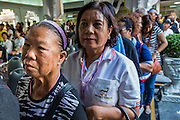 27 JANUARY 2014 - BANGKOK, THAILAND: People wait in line to mourn during bathing rites for Suthin Taratin at Wat Sommanat Rajavaravihara in Bangkok. In Thai tradition, after death a bathing ceremony takes place in which relatives and friends pour water over one hand of the deceased. Suthin was a core leader of the People's Democratic Force to Overthrow Thaksinism (Pefot), one of several organizations leading protests against the elected government of Thai Prime Minister Yingluck Shinawatra. He was murdered Sunday, Jan. 28, while he was leading a rally to prevent voters from reaching a polling center in the Bang Na district of Bangkok.     PHOTO BY JACK KURTZ