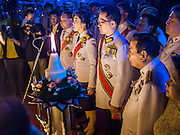 05 DECEMBER 2013 - BANGKOK, THAILAND: YINGLUCK SHINAWATRA (center) the Prime Minister of Thailand, reads a proclamation honoring the King while her husband, ANUSORN AMORNCHAT, stands next to her at the celebration of the birthday of the King in Bangkok. Thais observed the 86th birthday of Bhumibol Adulyadej, the King of Thailand, their revered King on Thursday. They held candlelight services throughout the country. The political protests that have gripped Bangkok were on hold for the day, although protestors did hold their own observances of the holiday. Thousands of people attended the government celebration of the day on Sanam Luang, the large public space next to the Grand Palace in Bangkok.     PHOTO BY JACK KURTZ