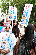 East End, London July 5th 2014. Rally and march against proposed cuts to National Health Service doctors' surgeries, specifically MPIG (Minimum Practice Income Guarantee payments) brought in to ensure practices in deprived areas had enough money to deliver high quality General Practice services. A group of women activists with placards listen to speeches.