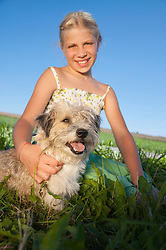 Girl (10-11) sitting with dog in meadow, portrait