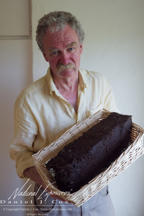 Charlie Troy holds a chunk of peat that was the material earlier generations of Ireland used to heat their homes.