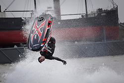 © licensed to London News Pictures. London, UK 12/01/2013. Multiple freestyle Jet Ski Champion Jack Moudle performing a jump stunt with a jet ski outside ExCeL London for London Boat Show visitors. Photo credit: Tolga Akmen/LNP