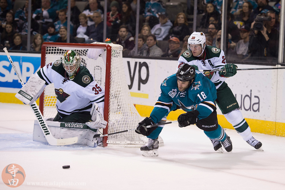 December 12, 2015; San Jose, CA, USA; San Jose Sharks right wing Mike Brown (18) passes the puck against Minnesota Wild defenseman Ryan Suter (20) and goalie Darcy Kuemper (35) during the second period at SAP Center at San Jose.
