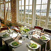 Tables are set for a rehearsal dinner as the marina is seen outside the windows at Historic Rice Mill in Charleston.   ©Travis Bell Photography