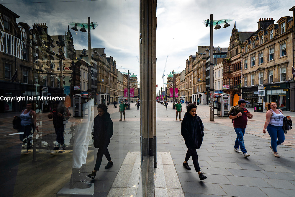 Glasgow, Scotland, UK. 12 June 2020. View of people on Buchanan Street pedestrian shopping zone reflected in shop window. Although shops can reopen in England next week , in Scotland the lockdown is not being relaxed so quickly with several more weeks of restrictions to go. Shops and businesses remain closed and streets are very quiet.  Iain Masterton/Alamy Live News