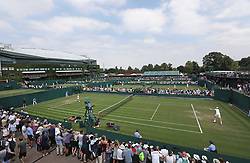 Spectators watch a match on court 8 on day three of the Wimbledon Championships at the All England Lawn Tennis and Croquet Club, Wimbledon.