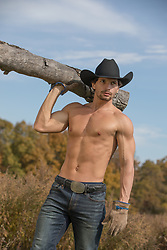 Shirtless sexy cowboy carrying wood