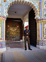 "UDAIPUR, INDIA - CIRCA NOVEMBER 2018: Guard of the City Palace in Udaipur. The city is the historic capital of the kingdom of Mewar. Surrounded by Aravali Range, which separates it from Thar Desert, and full of lakes Udapiur is also known as the ""City of Lakes"" and dubbed as the most romantic spot of the Indian Continent."