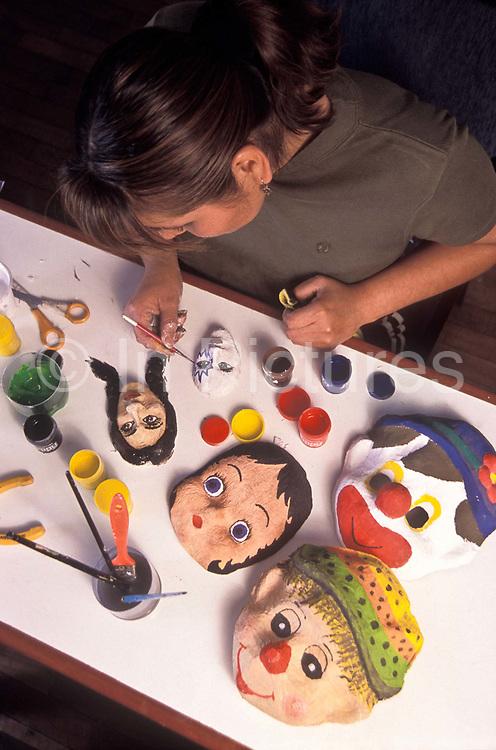A  teacher makes and paints Papier Mache masks as pasrt of her art lesson, Arequipa, Peru.