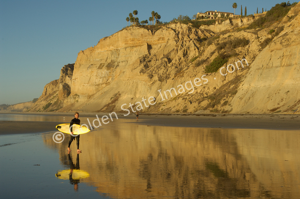 Surfers walk across tidal flats in late afternoon light. (Not Model Released)