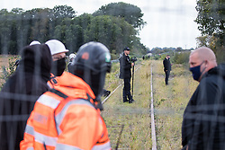 Steeple Claydon, 23rd September, 2020. National Eviction Team enforcement agents, security guards and Thames Valley Police officers watch tree surgeons working on behalf of HS2 Ltd fell a 200-year-old oak tree alongside the East West Rail route known locally as the '7 Sisters Oak' as part of works connected to the HS2 high-speed rail link. A small group of local people and anti-HS2 activists based at the nearby Poors Piece Conservation Project also observed the felling of the tree, which was home to bats and other species, whilst monitored by a joint force of around fifty bailiffs, security guards and police officers from Thames Valley Police.
