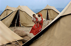 Ratno Devi and her two sons who were forced to migrate from their home in Pargwal, India prepare tents near Ahknoor in the Indian held state of Jammu and Kashmir, May 29, 2002. Indian and Pakistani troops continue to exchange heavy mortar, artillery and machine-gun fire along the line that divides Kashmir between them. India is pressing Pakistani President Pervez Musharraf to crack down on the flow of Muslim militants from Pakistan into Kashmir.