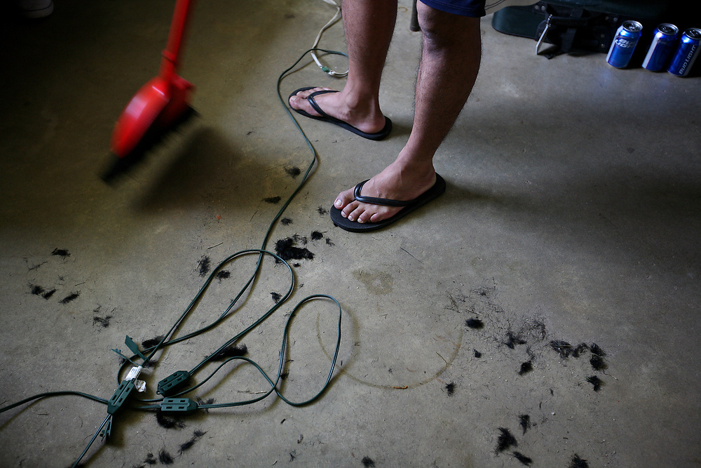 Migrant worker Francisco Melendres cleans up after getting his hair cut by housemate Eduardo Cruz in his bedroom at Titan Farms. Both men are from Nayarit, Mexico and have been working at the farm for one year.