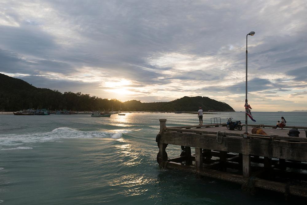 A man, woman, and child watch the setting sun from the pier at Chaloklum Bay, Ko Phangan, Thailand. (June 2017)