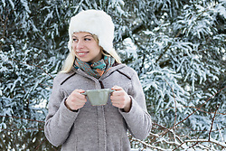 Teenage girl drinking coffee in winter season, Bavaria, Germany