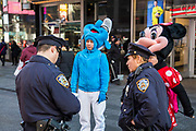 Two New York Police Officers interview two people dressed as life-size Smurf and Minnie Mouse on Time Square, Midtown Manhattan, New York City, New York, United States.  In 2016, Mayor de Blasio signed a law to declare pedestrian plazas, like Times Square to be no-soliciting zones due to the ongoing issues of costume characters harassing tourists for money.