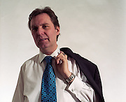 The British Rt. Hon. Alan Milburn, MP for Darlington is seen in a studio setting in an official Government room loacted in the Cabinet Office, Whitehall, London, England. In shirtsleeves he holds his jacket over his shoulder and wears a blue patterned tie. Milburn was a supporter of Tony Blair (and therefore called a Blairite) and held numerous governmental posts, including: Minister of State for Health (1997-1998); Chief Secretary to the Treasury (1998-1999); Secretary of State for Health (1999-2003) and Chancellor of the Duchy of Lancaster (2004 to 2005). Source: www.alanmilburn.co.uk.