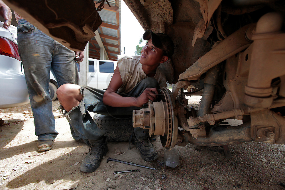 Jonathan Canhadia, 19, listens to his boss give him instructions on what this pickup up needs.  A makeshift mechanic shop sits in the center of Guaimaca, reparing any type of vehicles.  Automobiles are few and most are recycled in an effort to keep them going. Honduras is considered the third poorest country in the Western Hemisphere (Haiti, Nicaragua). With over 50% of the population living below the poverty line and 28% unemployed, Hondurans frequently turn to illegal immigration as a solution to their desperate situation. The Department of Homeland Security has noted an 95% increase in illegal immigrants coming from Honduras between 2000 and 2009, the largest increase of any country.