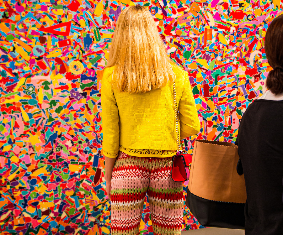 Blonde on blonde woman checks out colorful and intricate painting at Art Basel Miami Beach