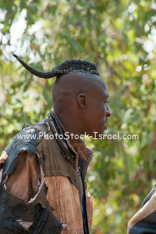 Himba man with traditional hair. The Himba are a pastoral and nomadic people of northern Namibia. They tend herds of goats and cattle in the arid desert environment, living in extended families in homesteads. Both men and women go topless. Photographed in Namibia, Southern Africa.