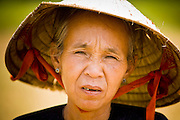 10 MARCH 2006 - TAY NINH, VIETNAM: A peasant woman in a field in Tay Ninh province, Vietnam. The rice was harvested months ago and the woman came back to go through the field a final time to look for rice she could sell for extra money for her family. Photo by Jack Kurtz