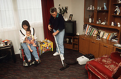 Woman with disability; who is wheelchair user; holding baby on knee while carer hoovers floor,