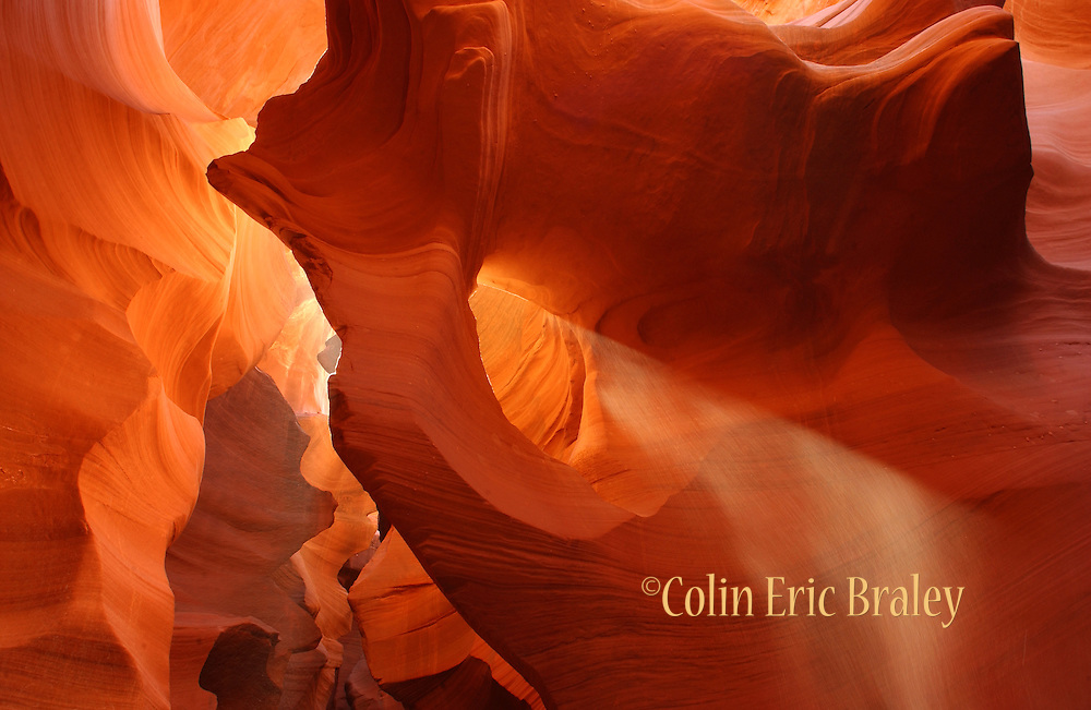 The sandstone of Lower Antelope Canyon glows as sand falling from the surface passes through the sunlight creating a beam effect.. This slot canyon is located on Navajo land near Page, Arizona.