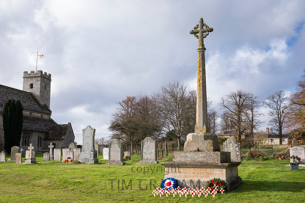 Remembrance wreaths and crosses with poppies at war memorial for The Great War 1914-1918 - World War I and World War II 1939-1945 in the graveyard of St Mary's Church, Swinbrook commemorating those who died from the parish of Swinbrook and Widford, Oxfordshire, UK