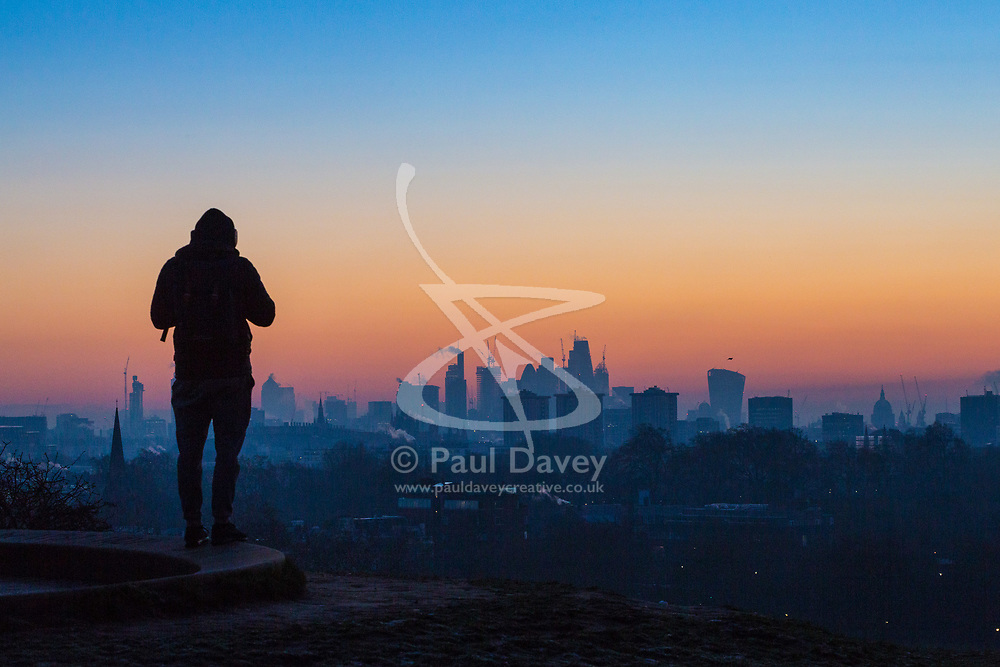 London, December 12 2017. An early morning walker awaits the sunrise on a clear very cold morning in London, seen from Primrose Hill in Camden. © Paul Davey