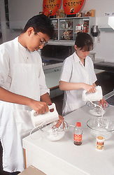 Secondary school pupils using electric whisks during home economics lesson,