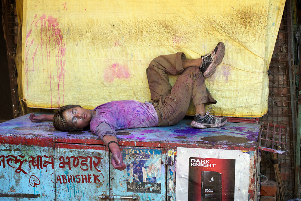 Varanasi, India. Exhausted, this young Indian Man is resting on a street stall after a full day of crazy celebration for the Holy Festival.