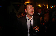 A London office worker sings out loud during a karaoke night at a City of London wine bar. Grasping a glass of an unknown drink, he shouts out the words during this evening of after-work merriment where friends and associates gather to share alcohol and fun.
