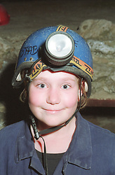 Portrait of teenage girl wearing safety helmet and head torch potholing in cave,