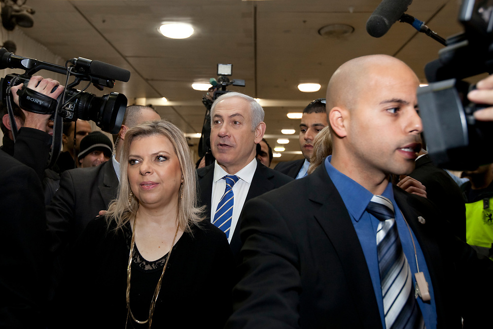Israel's Prime Minister and Likud party leader Benjamin Netanyahu (C) and his wife Sara, leave a polling station in Jerusalem, Israel, on January 31, 2012, after casting their votes for the Likud party primary elections.