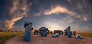 "Carhenge sunrise. Carhenge replicates England's Stonehenge using vintage American automobiles, near Alliance, Nebraska, in the High Plains region, USA. After studying Stonehenge in England, years later, Jim Reinders recreated the physical size and placement of Stonehenge's standing stones in summer 1987, helped by 35 family members. Reinders said, ""It took a lot of blood, sweat, and beers."" Carhenge was built as a memorial to Reinders' father. 39 automobiles were arranged in the same proportions as Stonehenge with the circle measuring a slightly smaller 96 feet (29m) in diameter. Some autos are held upright in pits five feet deep, trunk end down, while other cars are placed to form the arches and welded in place. All are covered with gray spray paint. The heel stone is a 1962 Cadillac. Reinders donated Carhenge to the Friends of Carhenge, who gifted it to the Citizens of Alliance in 2013. This image was stitched from multiple overlapping photos."