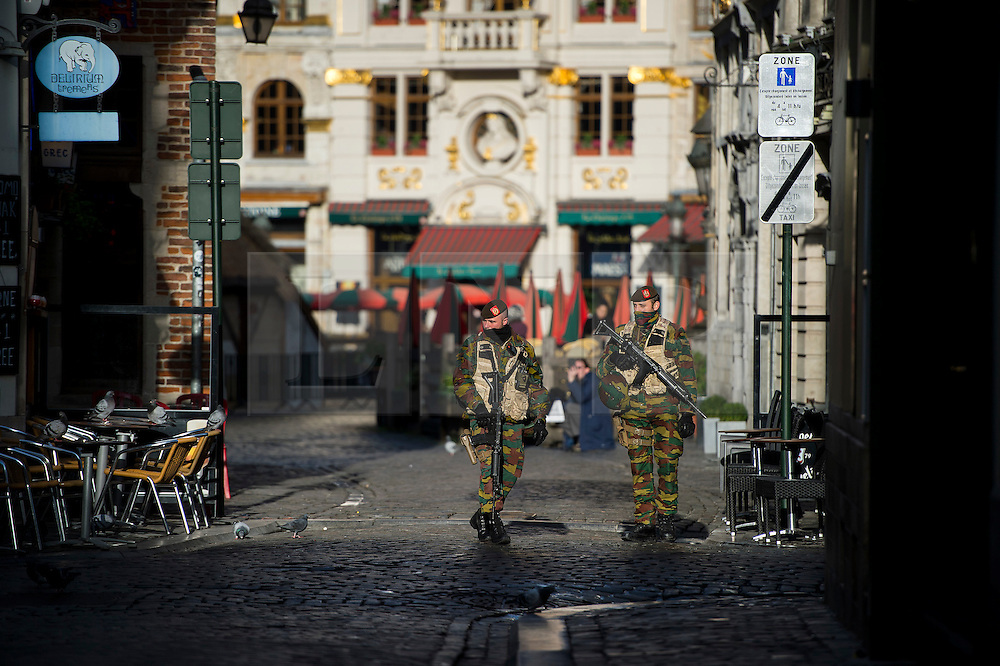 """© Licensed to London News Pictures. 23/11/2015. Brussels, Belgium. Belgian military walk past An empty restaurant at lunchtime on a deserted street in central Brussels where the city is currently on """"lockdown"""" amid """"imminent threat"""" of Paris-style bomb and gun attacks. Photo credit: Ben Cawthra/LNP"""