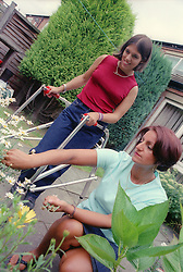 Girl with Cerebral Palsy using walking frame and mother gardening,