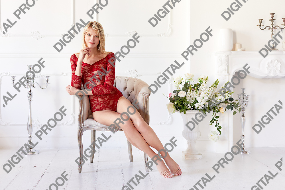 Gorgeous woman in a red lace bodysuit and barefoot sitted in a chair with frontal look in a white interior room.  Women boudoir concept.