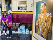 """05 DECEMBER 2013 - BANGKOK, THAILAND:  With a portrait of Bhumibol Adulyadej, the King of Thailand, in the foreground, women wait to board a special train on the 86th birthday of Bhumibol Adulyadej, the King of Thailand. Dec. 5, the King's Birthday, is a national holiday in Thailand, and is also celebrated as the country's """"Fathers' Day."""" The State Railways of Thailand put on special trains to take people to the King's """"Summer Palace"""" in the oceanside community of Hua Hin where the King granted a public audience. There were also merit making ceremonies throughout the country. Many people wear yellow on the King's Birthday because yellow is the color associated with his reign. As of 2013, he was the longest reigning monarch in the world.     PHOTO BY JACK KURTZ"""