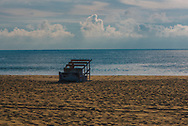 A life guard chair on its side on the beach early in the morning.