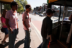 Youths getting on  a bus.