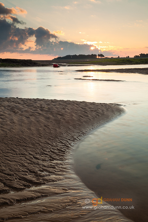 Sunrise at low tide on the North Norfolk coast. Captured on Wells beach looking out to an isolated crop of trees on East Hills. North Norfolk coast, East Anglia.