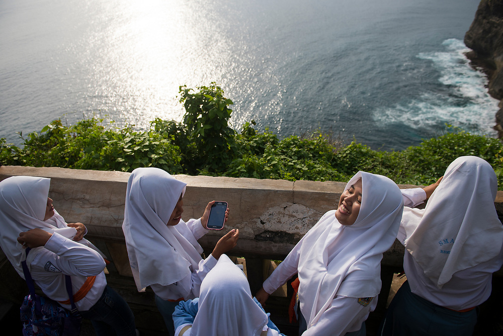Bali, Indonesia - February 21, 2017: Muslim school girls, one holding a Samsung smartphone, visit famous Uluwatu Temple, with its dramatic sea view, on the Indonesian island of Bali.