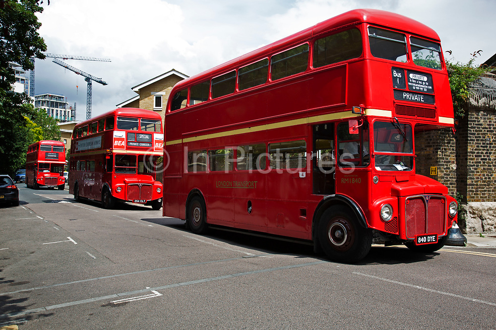 Three private hire red Routemaster London buses passing through Wapping in London, England, United Kingdom. The AEC Routemaster is a double-decker bus designed by London Transport and built by the Associated Equipment Company AEC and Park Royal Vehicles. The first prototype was completed in September 1954 and the last one was delivered in 1968.